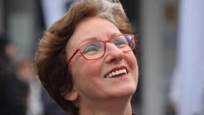Eine Frau mit roter Brille lacht freudig