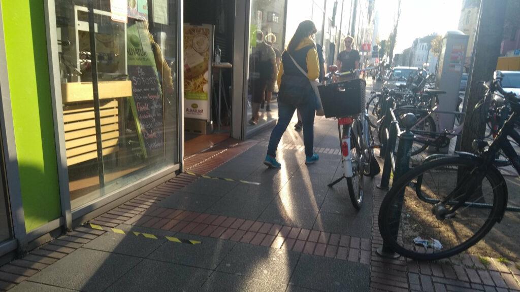 Eine Frau läuft den schmalen Gehweg entlang