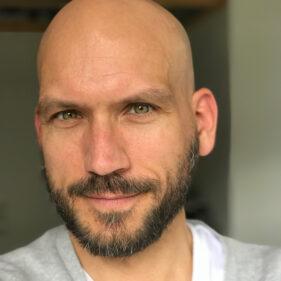 Ein Mann mit Glatze und Vollbart