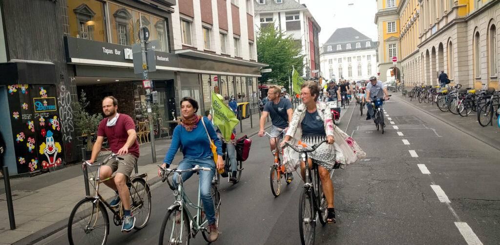 Ein Verband von Radfahrendnen fährt am Uni-Hauptgebäude vorbei. Manche haben Fahnen vom Radentscheid Bonn an ihren Fahrrädern.