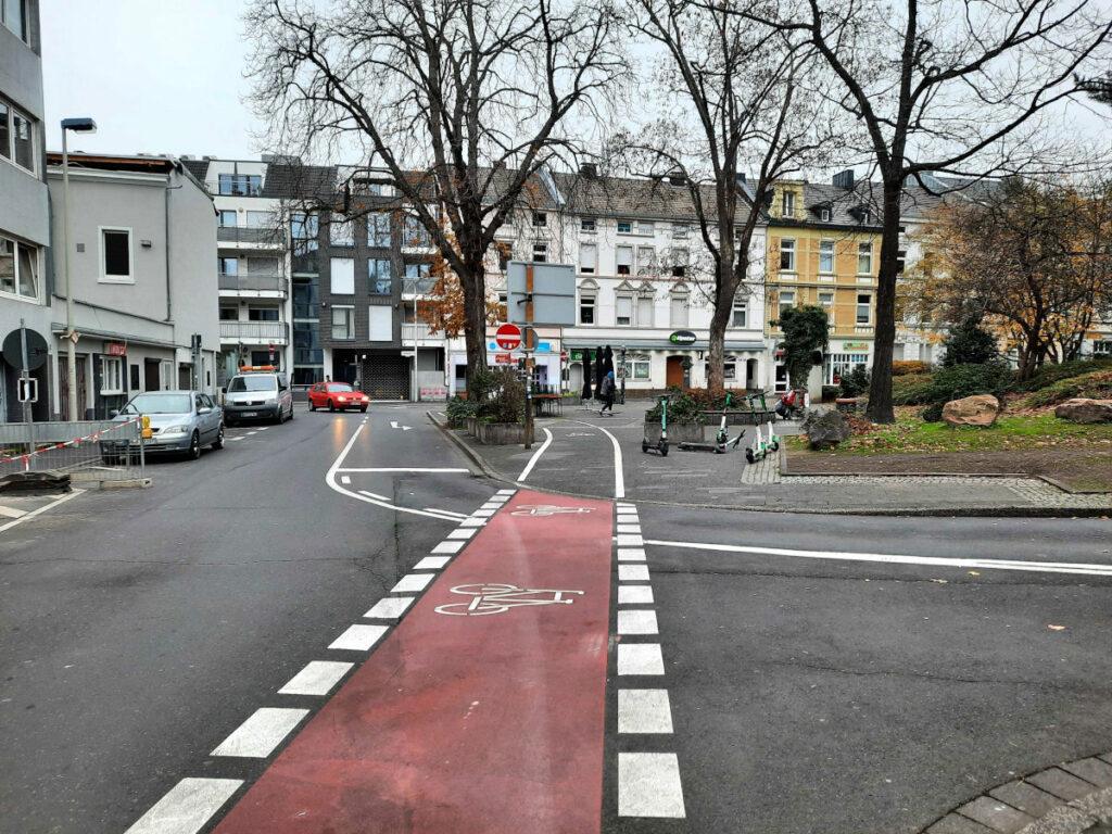 Ein Radweg führt von der Straße weg auf einen angrenzenden Platz um von dort wieder auf die Straße zu führen