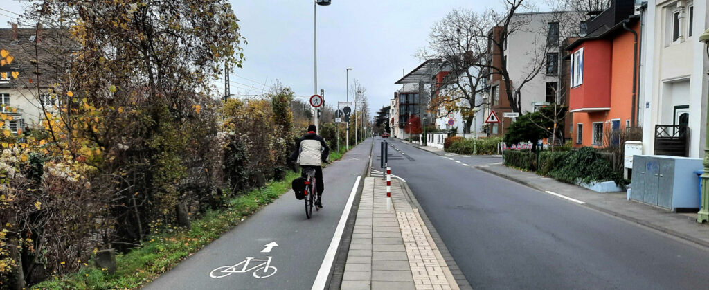 Ein Mann fährt auf einem linksseitig geführten Radweg