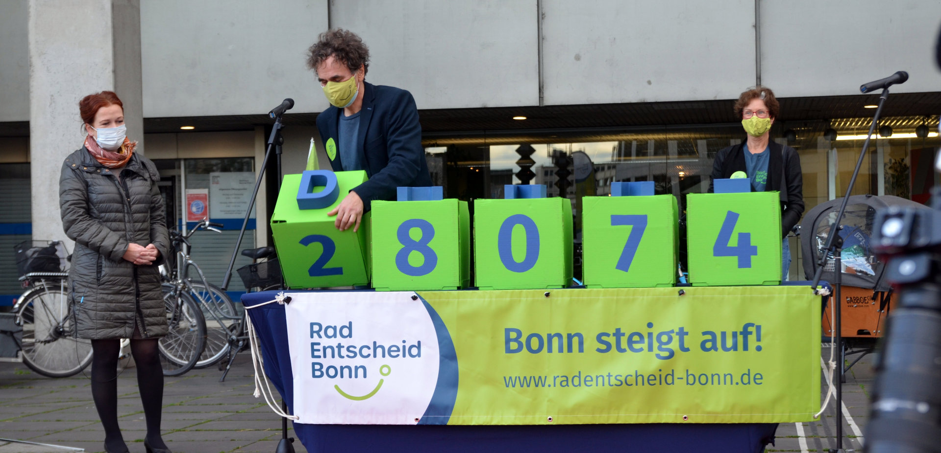 Ein Mann dreht Kisten um, sodass die Zahl 28.074 erscheint.