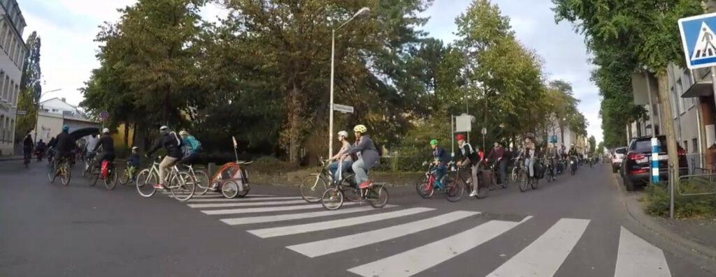 Eine lange Reihe Fahrradfahrende fahren über eine Kreuzung
