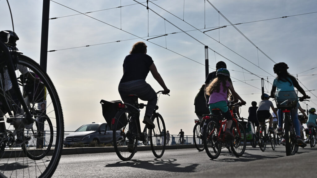 Große und kleine Radfahrer:innen fahren über die Kennedybrücke