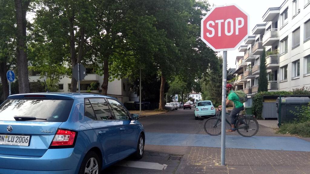 Ein blaues Auto hält an einem Stopp-Schild während der querende Radverkehr Vorfahrt hat