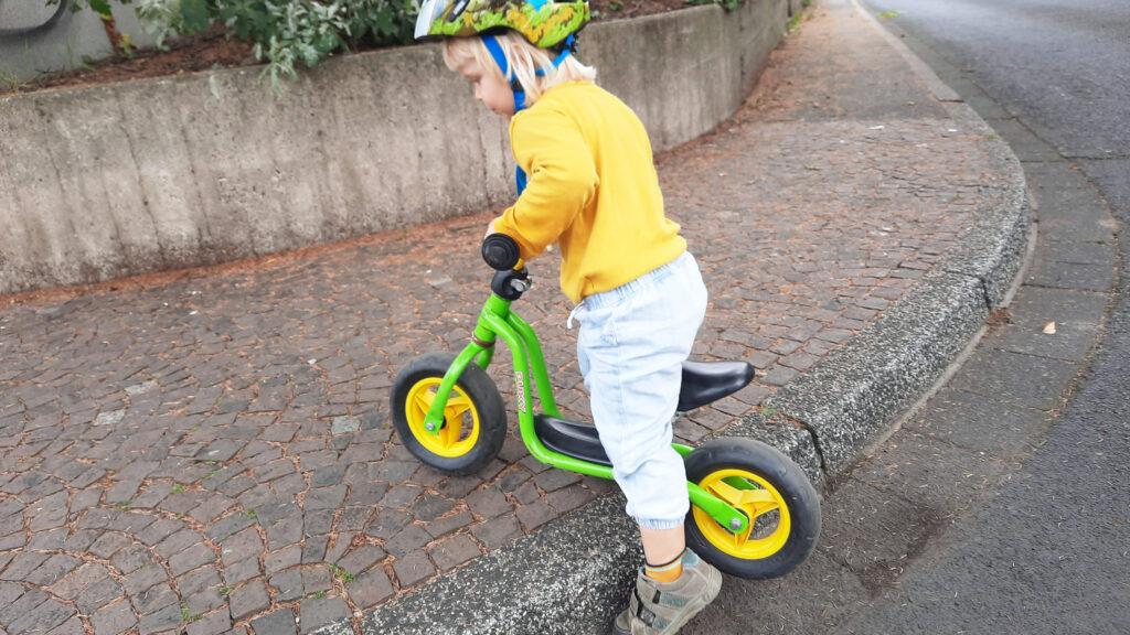 Ein Kind versucht mit seinem Laufrad über einen hohen Boardstein auf den Gehweg zu kommen