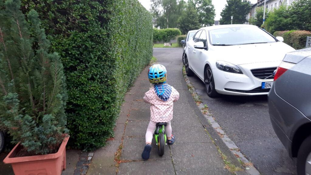 Ein Kind fährt mit seinem Laufrad auf einem Gehweg